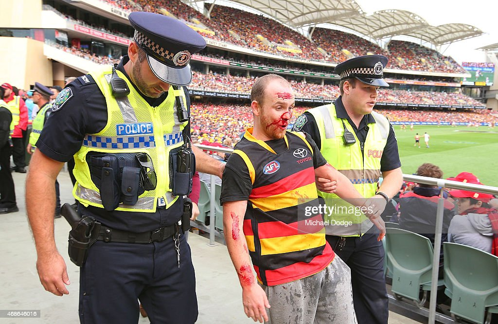 A Crows fan is taken away by Police after a punch up during the round one AFL match between the Adelaide Crows and the North Melbourne Kangaroos at Adelaide Oval on April 5, 2015 in Adelaide, Australia.
