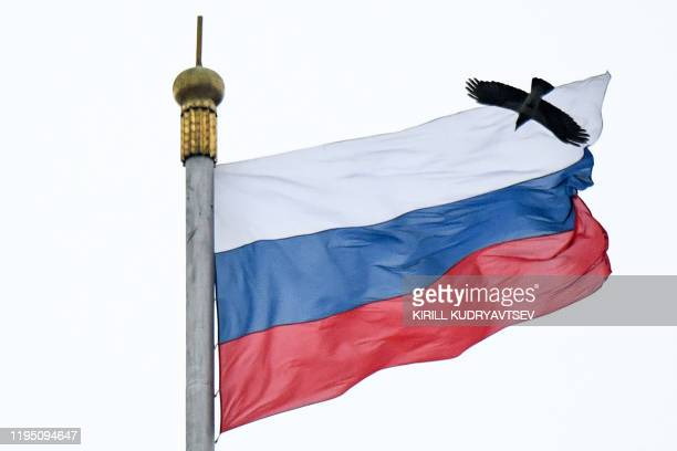 Crows fly close to a Russian flag at the top of the Russian Government building in downtown Moscow on January 21 2020 Prime Minister Mikhail...