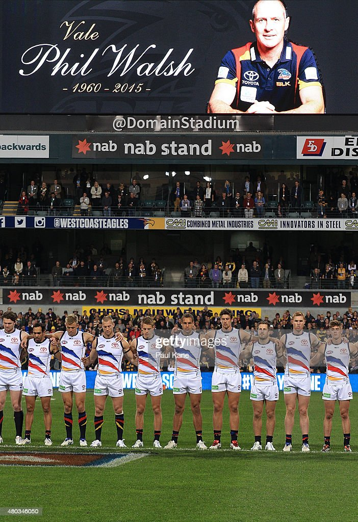 Crows players line up for a moments silence to pay respect to their coach Phil Walsh during the round 15 AFL match between the West Coast Eagles and the Adelaide Crows at Domain Stadium on July 11, 2015 in Perth, Australia.