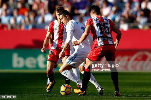 Crsitiano Ronaldo of Real Madrid competes for the ball with Juanpe Ramirez of Girona during the La Liga match between Girona and Real Madrid at...