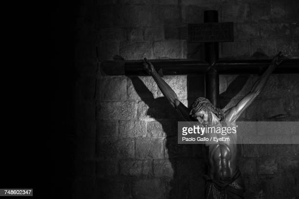 Crucifix Against Wall In Darkroom