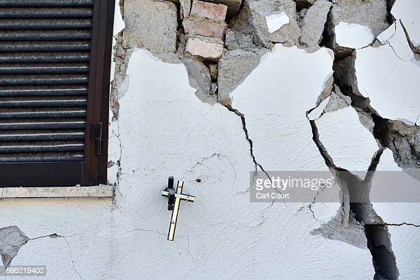 A crucifix hangs on the wall of a damaged house on August 25 2016 in Amatrice Italy The death toll in the 62 magnitude earthquake that struck around...