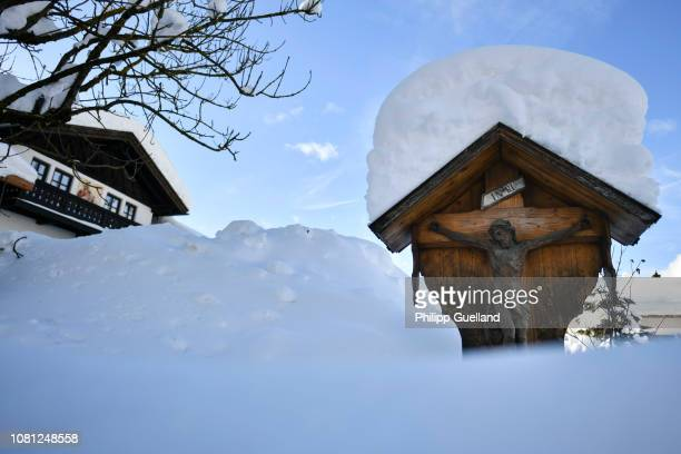 A crucifix is covered by snow following heavy snowfall in the area on January 12 2019 in Kruen Germany Exceptionally high levels of snow have closed...