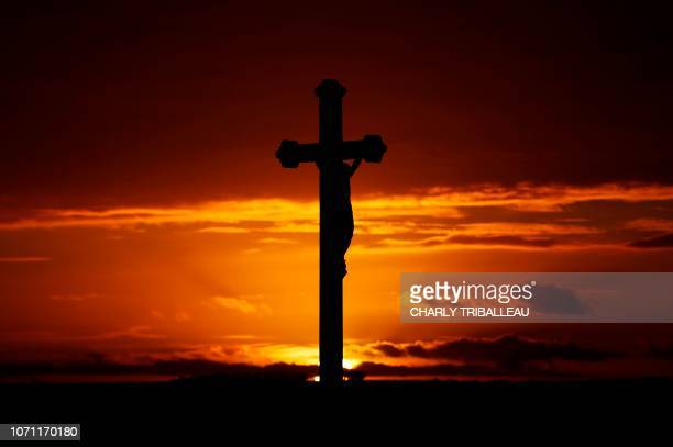 A crucifix is pictured at sunset in Ernes northwestern France on December 10 2018