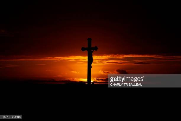 Crucifix is pictured at sunset in Ernes, northwestern France on December 10, 2018.