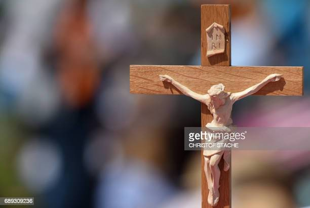 A crucifix is seen during the final mass of the Kirchentag festival celebrating the 500th anniversary of the Reformation at a meadow near the river...