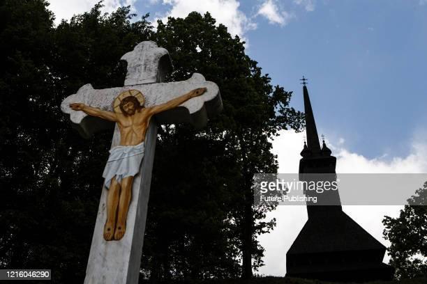 Crucifix is seen near the 14m spire the wooden Saint Nicholas Church built in 1779, Danylovo village, Khust district, Zakarpattia Region, western...