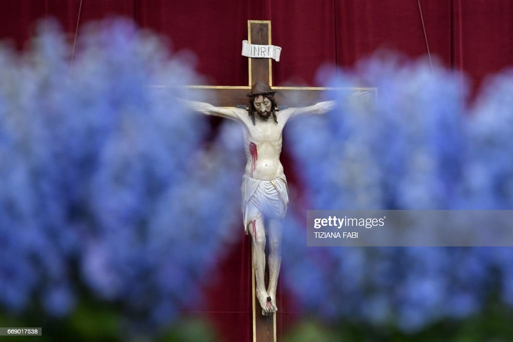 A crucifix is seen through flowers adorning St Peter's square before the Easter Sunday mass on April 16, 2017 in Vatican. Christians around the world are marking the Holy Week, commemorating the crucifixion of Jesus Christ, leading up to his resurrection on Easter. / AFP PHOTO / Tiziana FABI
