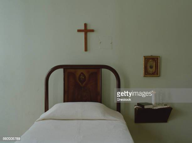 crucifix over bed in simple bedroom - crucifix stock pictures, royalty-free photos & images