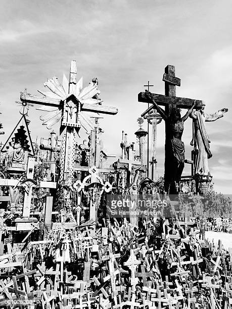 Crucifixes At Hill Of Crosses Against Cloudy Sky