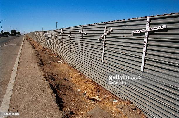 Crucifixes line the US -Mexico border fence just outside of Tijuana in memory of those who died whilst trying to cross it. Most deaths occur much...