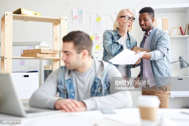 cruel multiethnic office colleagues discussing new employee: woman with blond hair whispering in coworkers ear while he pointing at man sitting at table - cruel stock pictures, royalty-free photos & images