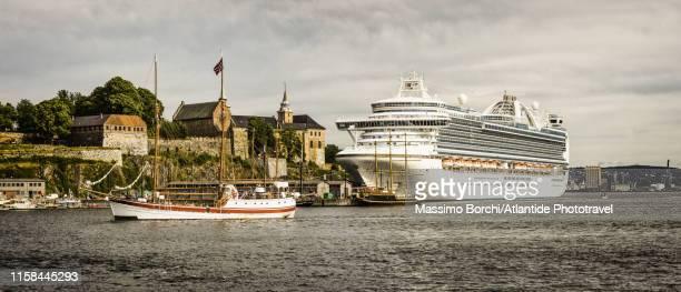 cruise boat near akershus fortress and castle - image stockfoto's en -beelden