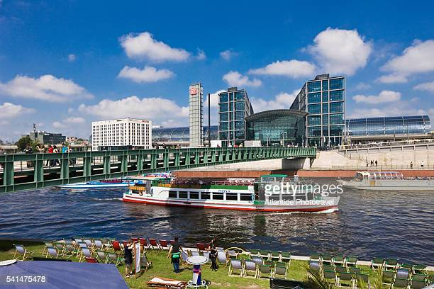 Cruise boat on Spree River, on the foreground a beach, on the background the Berlin Hauptbahnhof (Central Station)