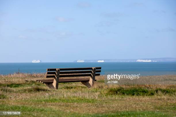 Cruise Liners in the distance berthed along the Dorset coast from Barton in the New Forest on September 27, 2020 in Hampshire, England.