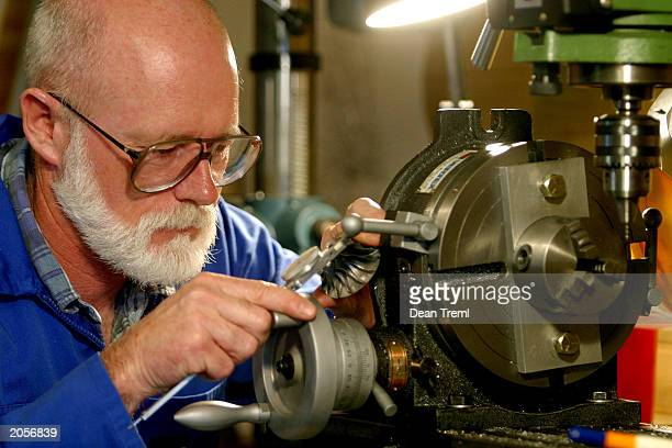 Cruise missile builder Bruce Simpson measures a turbine wheel in his backyard workshop in South Head June 5 2003 in New Zealand Simpson is building...