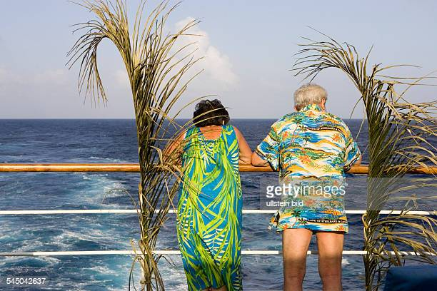 Cruise ship MS Astor in the Caribbean. Passenger leaning on the railing . Man wears an aloha shirt - only-editorial-use