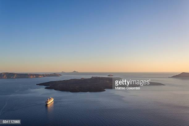 Cruise ship at sunset near volcano, Santorini