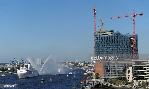 Cruise ship MS Deutschland runs into port past the construction site of the Elbe Philharmonic Hall Port with more than 200 members of the German...