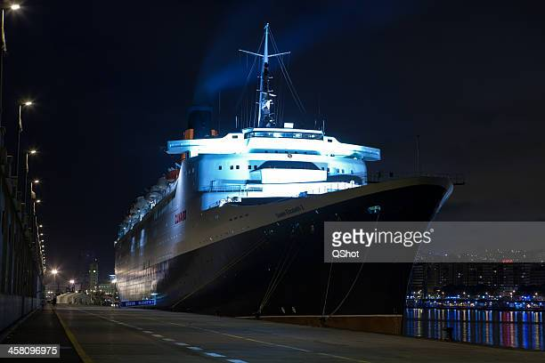 cruise ship in port at night - rms queen elizabeth 2 stock photos and pictures