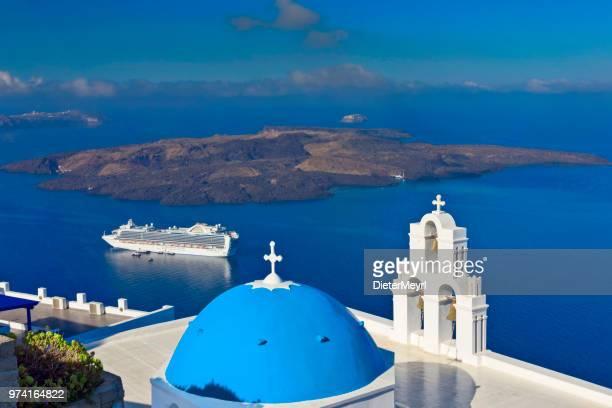 Cruise ship in Santorini with church tower, Greece