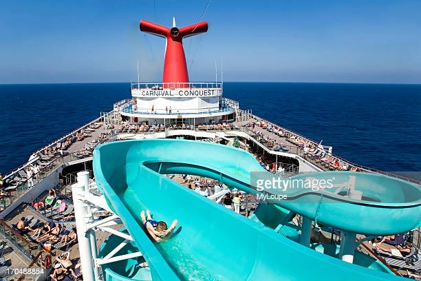 Cruise ship Lido deck with sun and swimming pool passengers enjoying the sun bathing and sunshine boy sliding down water slide cruise out of...