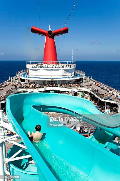 Cruise ship Lido deck with sun and swimming pool passengers enjoying the sun bathing and sunshine Boy sliding down water slide sitting up cruise out...