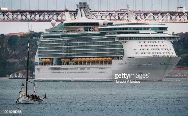 Cruise ship MS Navigator of the Seas operated by Royal Caribbean International sails past 25 de Abril bridge while leaving harbor on July 19 2018 in...