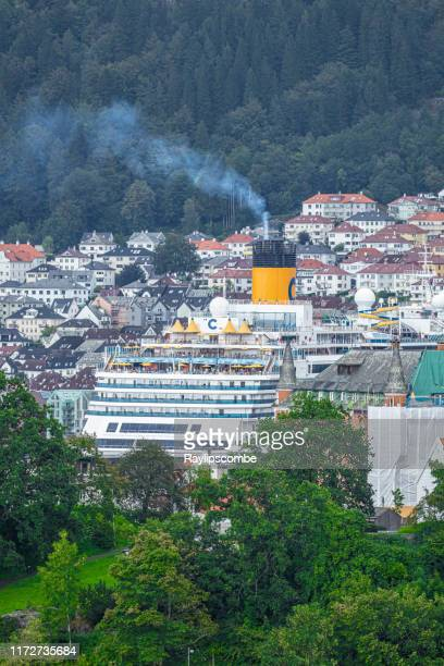 cruise ship nestled amongst the town houses of bergen in norway with smoke emitting from its funnel - ship funnel stock photos and pictures