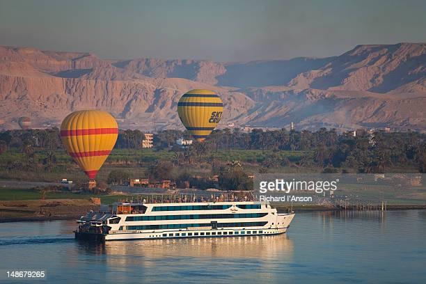 Cruise ship on Nile River & hot air balloons at sunrise.