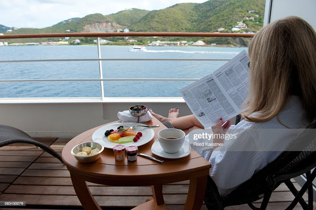 A cruise ship passenger relaxes  while reading the paper over coffee. : Stock Photo
