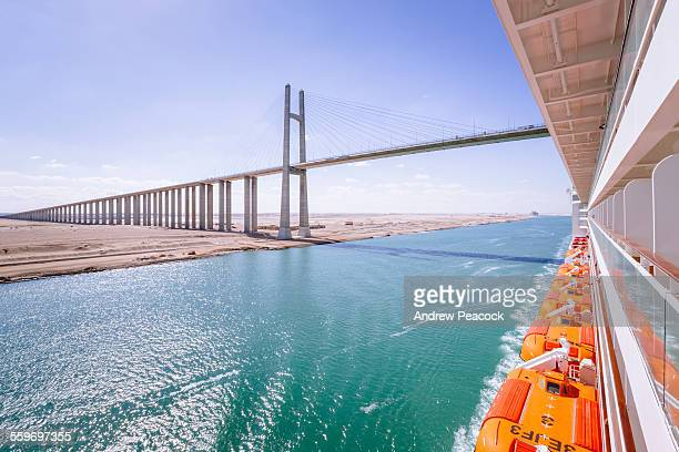cruise ship passes the suez canal bridge - suez canal stock photos and pictures