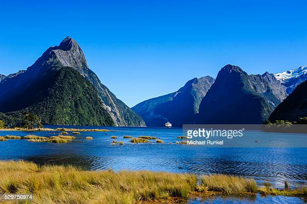 cruise ship passing through milford sound, fiordland national park, unesco world heritage site, south island, new zealand, pacific - international landmark stock pictures, royalty-free photos & images