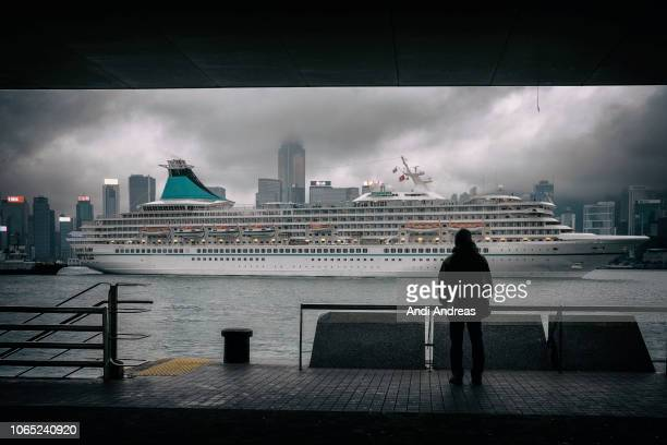 cruise ship passing victoria harbor hong kong with dramatic clouds over hong kong island - hong kong stock pictures, royalty-free photos & images