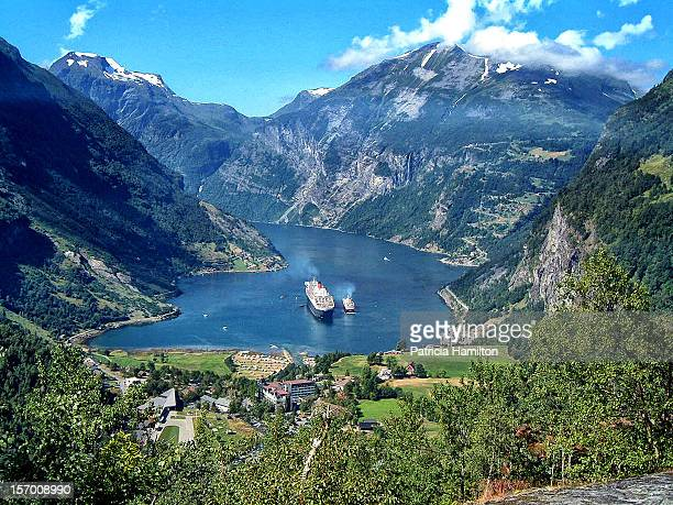 Cruise ship QM2 and te Norwegian coastal steamer side by side in the tourist attraction of Geiranger fjord which is one of Norway's most popular...