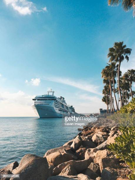 cruise ship sailing on sea against blue sky - cruise ship stock pictures, royalty-free photos & images
