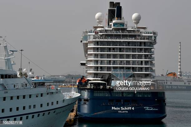 Cruise ships are docked at the passenger terminal in the port of Piraeus on October 18, 2018. - Chinese shipping giant Cosco said it has ambitious...
