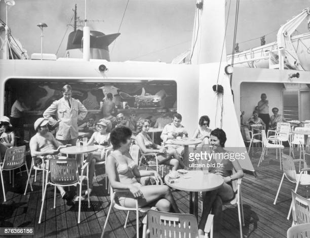 Cruise ships sea voyage passengers in swiimming costumes having drinks in the Viking Bar on board of MS Dana Sirena ferry ship