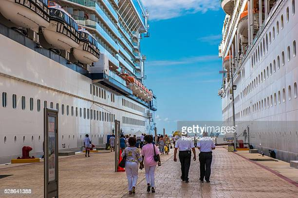 Cruise ships tower over returning passengers in Cozumel, Mexico