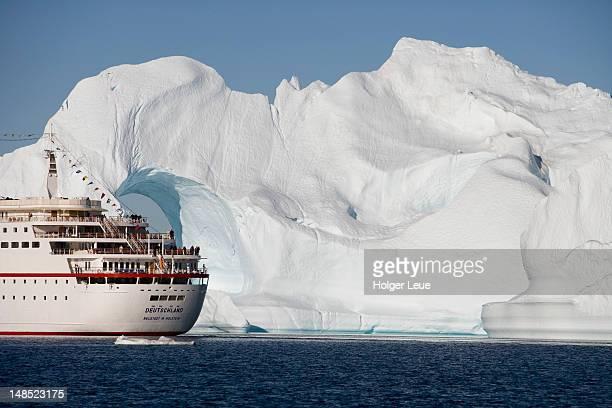 Cruiseship MS Deutschland and iceberg with hole from Ilulissat Kangerlua Icefjord.