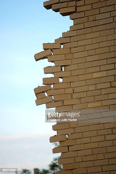 Crumbling brick wall against blue sky