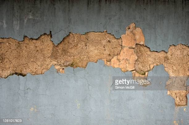 crumbling concrete stucco building exterior wall with peeling weathered light grey paint - deterioration stock pictures, royalty-free photos & images