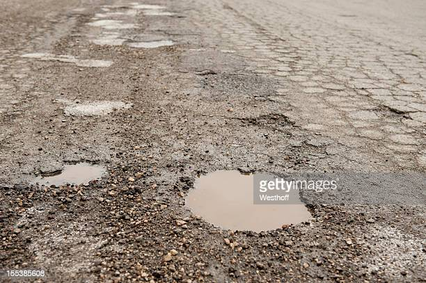 crumbling roadbed - pothole stock photos and pictures