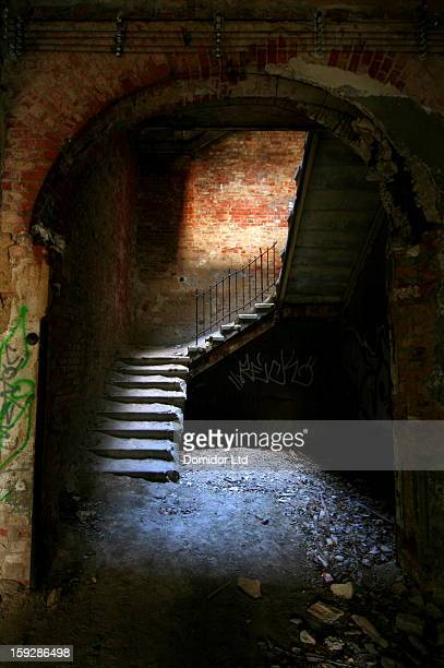 Crumbling staircase in a decaying building, lit by a pool of natural light from above.