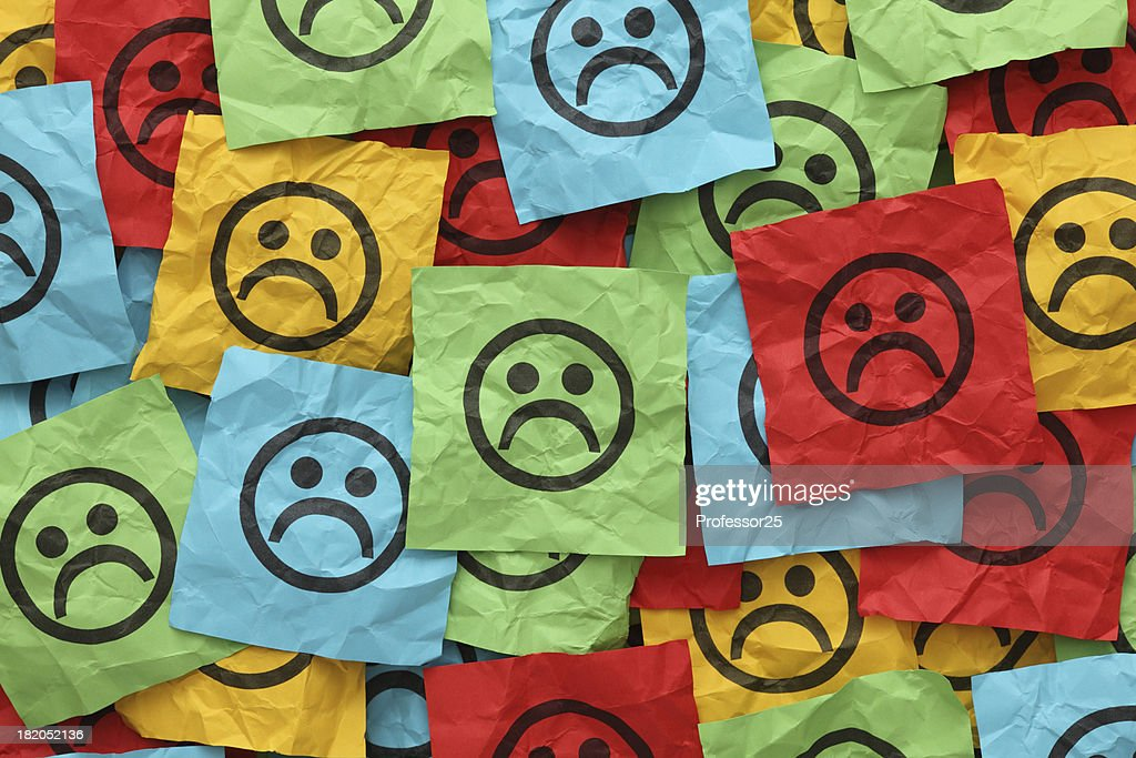 Crumpled adhesive notes with sad faces : Stock Photo