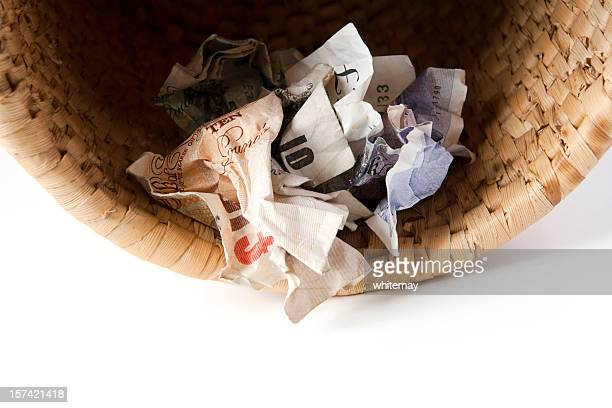 crumpled banknotes in waste basket - ten pound note stock photos and pictures