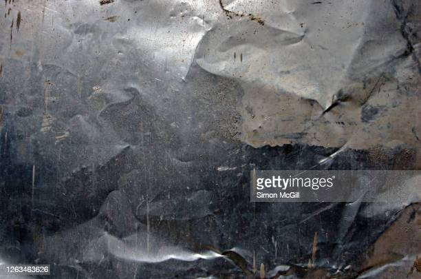 crumpled, dented, scratched and mud splattered stainless steel metal sheet - metallic stock pictures, royalty-free photos & images