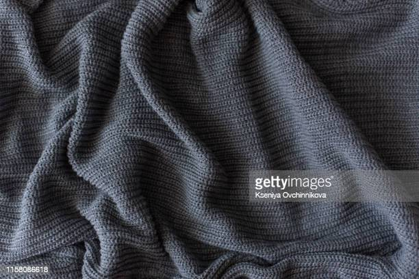 crumpled gray knitted blanket. soft and warm fabric crumpled in folds. texture for background or illustrations - blanket stock pictures, royalty-free photos & images