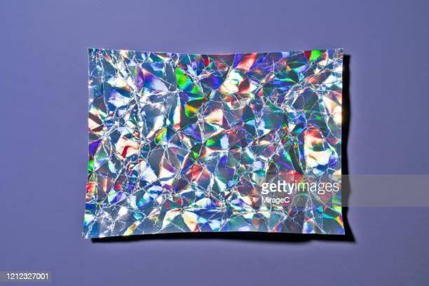 crumpled holographic foil on purple - 玉虫色 ストックフォトと画像