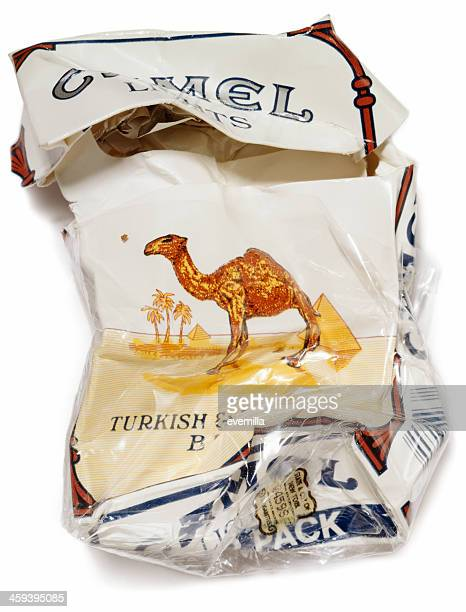 crumpled packet of camel cigarettes on white - cigarette pack stock pictures, royalty-free photos & images